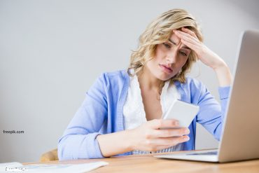 mulher usando celular e computador preocupada